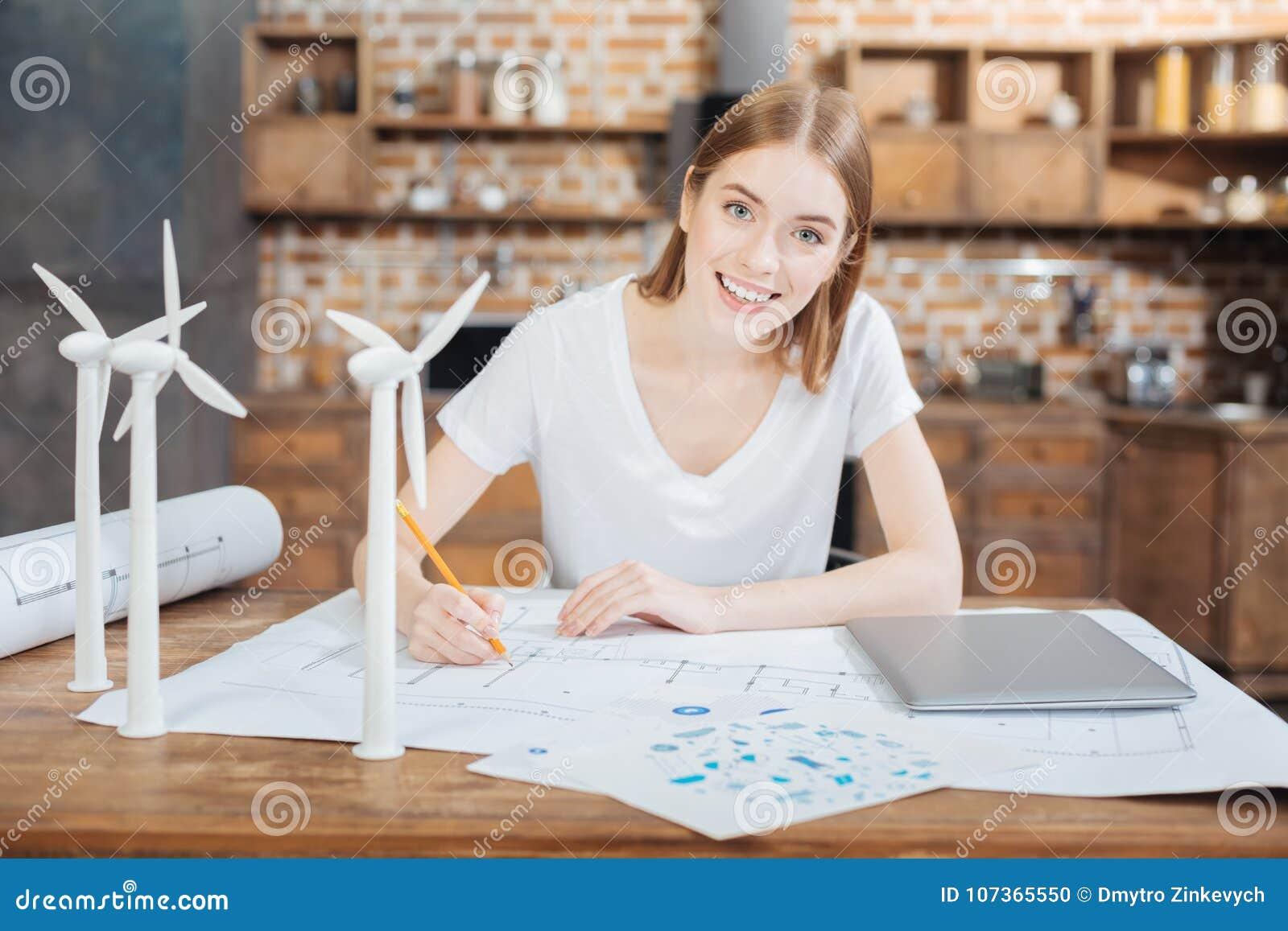 Giovane ingegnere positivo che sorride mentre sedendosi alla tavola ed al disegno