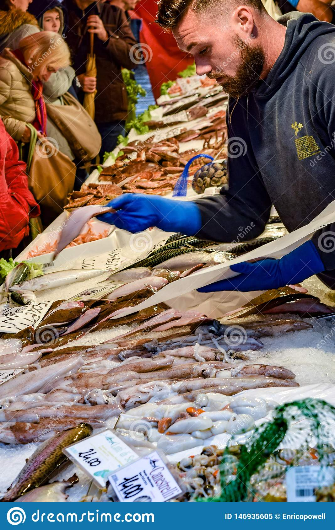 Giovane lavoratore maschio caucasico del mercato ittico che presente al cliente al mercato di Rialto, Venezia, Italia