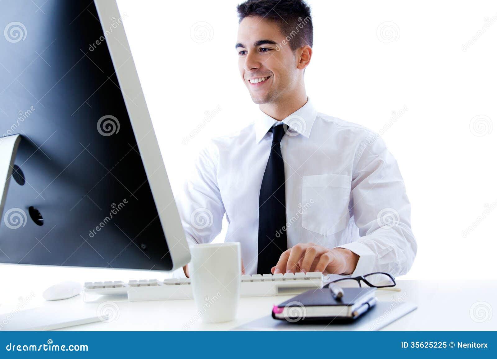 Giovane lavoro felice dell uomo di affari in ufficio moderno sul computer