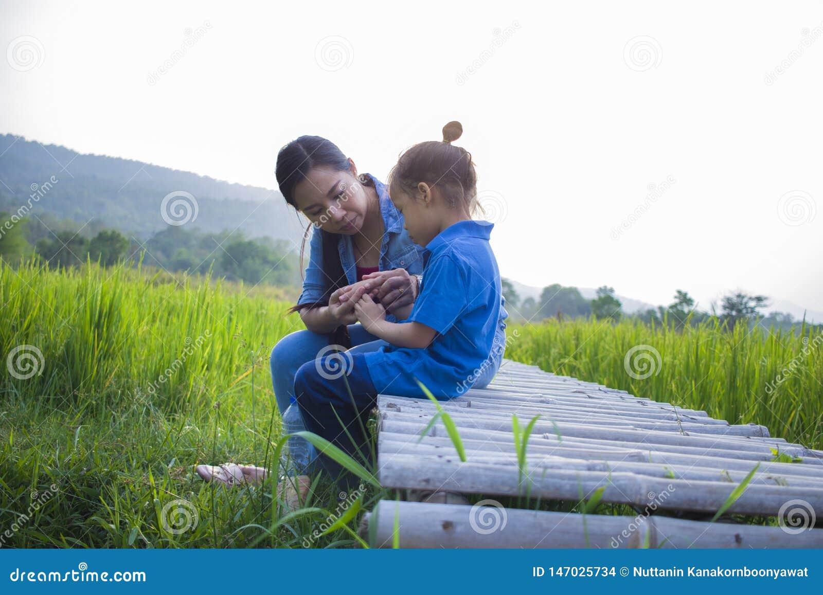 Giovane madre che abbraccia e che lenisce un piccolo ragazzo lungo gridante dei capelli, una madre asiatica provanti a confortare