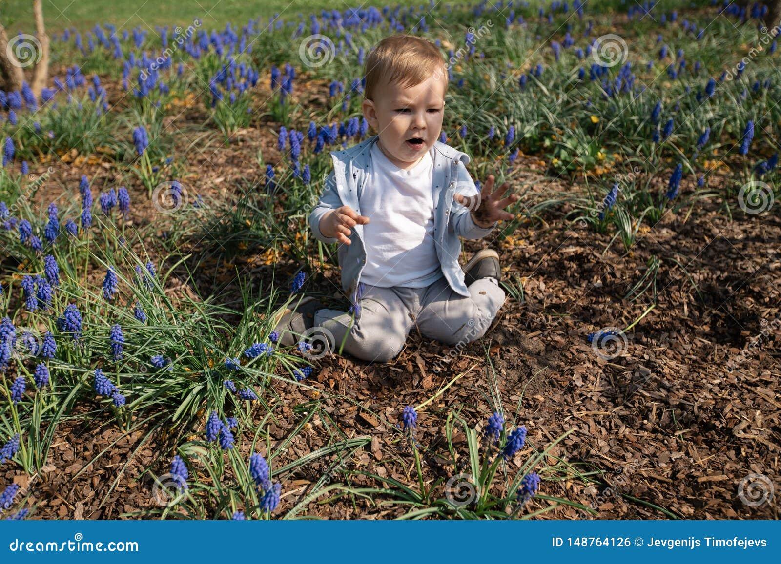 Giovane madre che gioca e che parla con un figlio del neonato su un campo del muscari in primavera - giorno soleggiato - giacinto