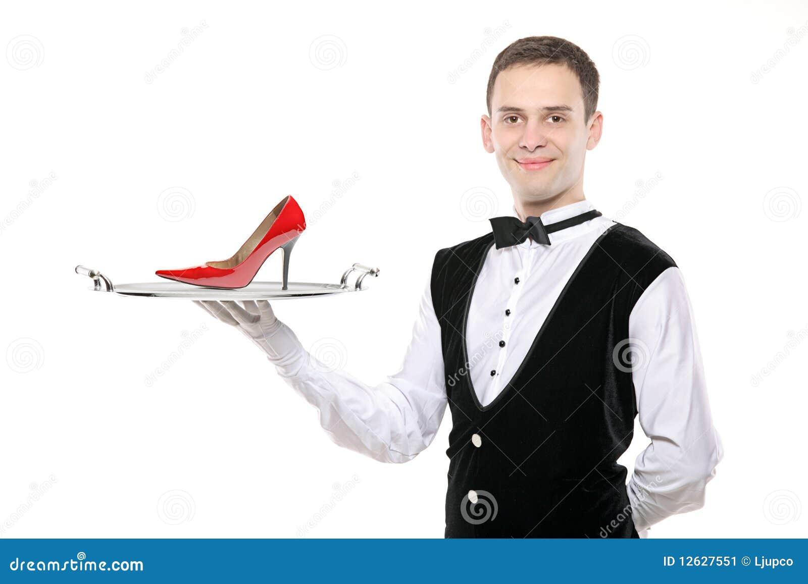 Giovane maggiordomo che tiene un cassetto con un alto tallone su esso
