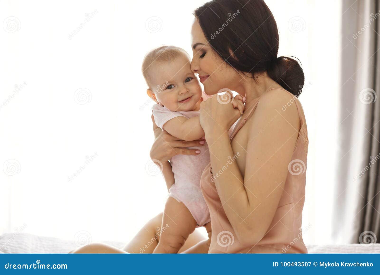 Giovane mamma attraente nell abbracciare sorridente degli indumenti da notte baciando il suo fare da baby-sitter a letto sopra la
