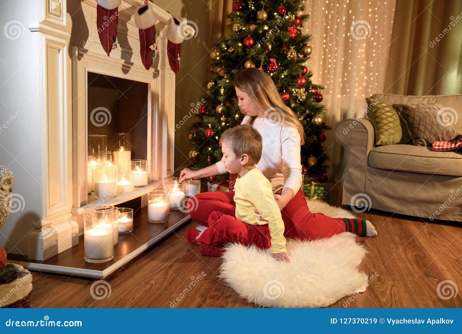 Giovane mamma che accende le candele con il suo piccolo figlio