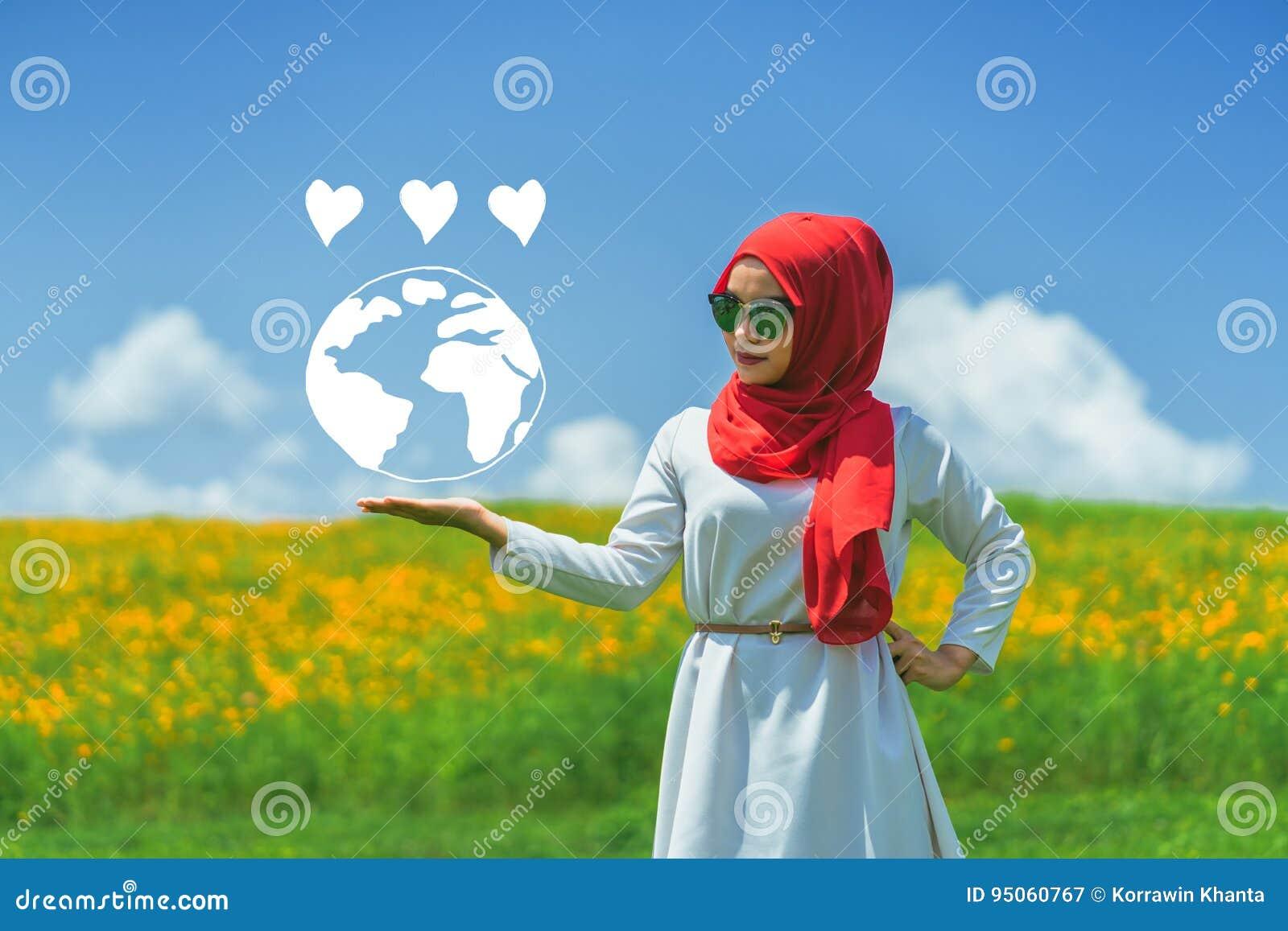 Giovane mano musulmana felice della donna che mostra la terra di amore