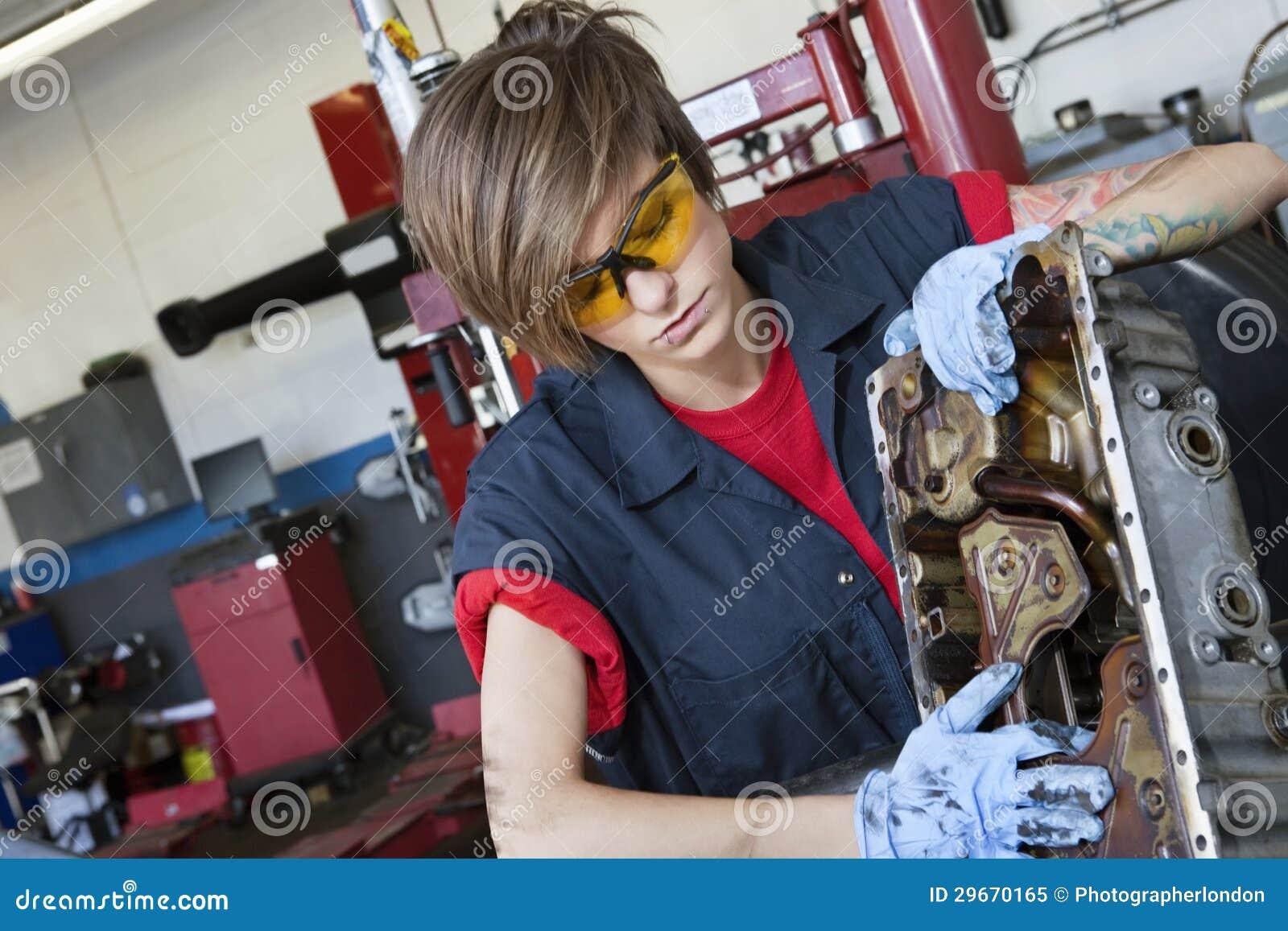 Giovane meccanico femminile che lavora al pezzo meccanico dell automobile in cantiere