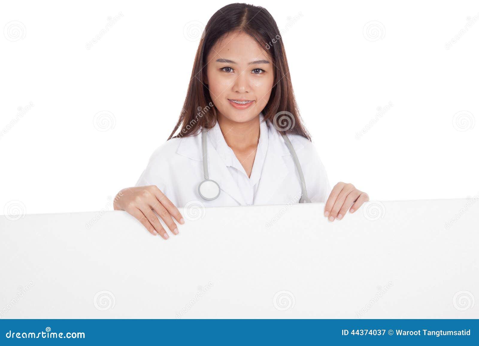 Giovane medico femminile asiatico che sta dietro il tabellone per le affissioni bianco in bianco