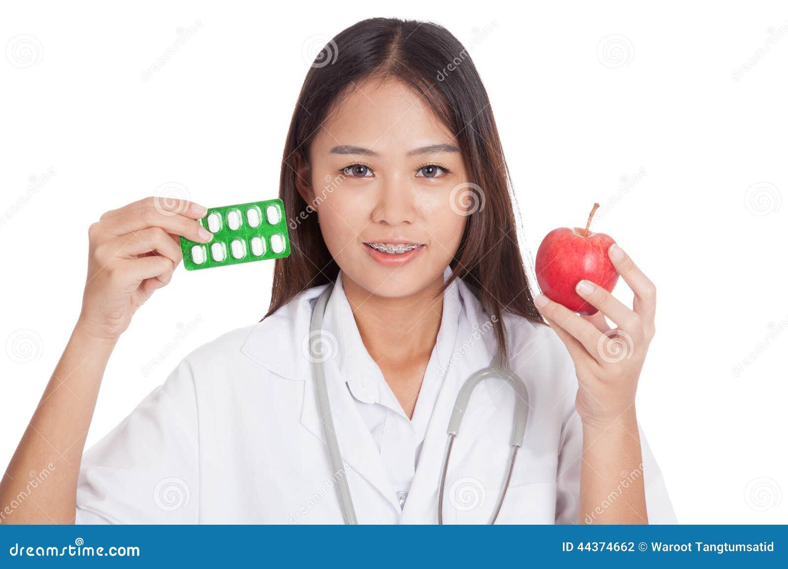 Giovane medico femminile asiatico con le pillole e la mela