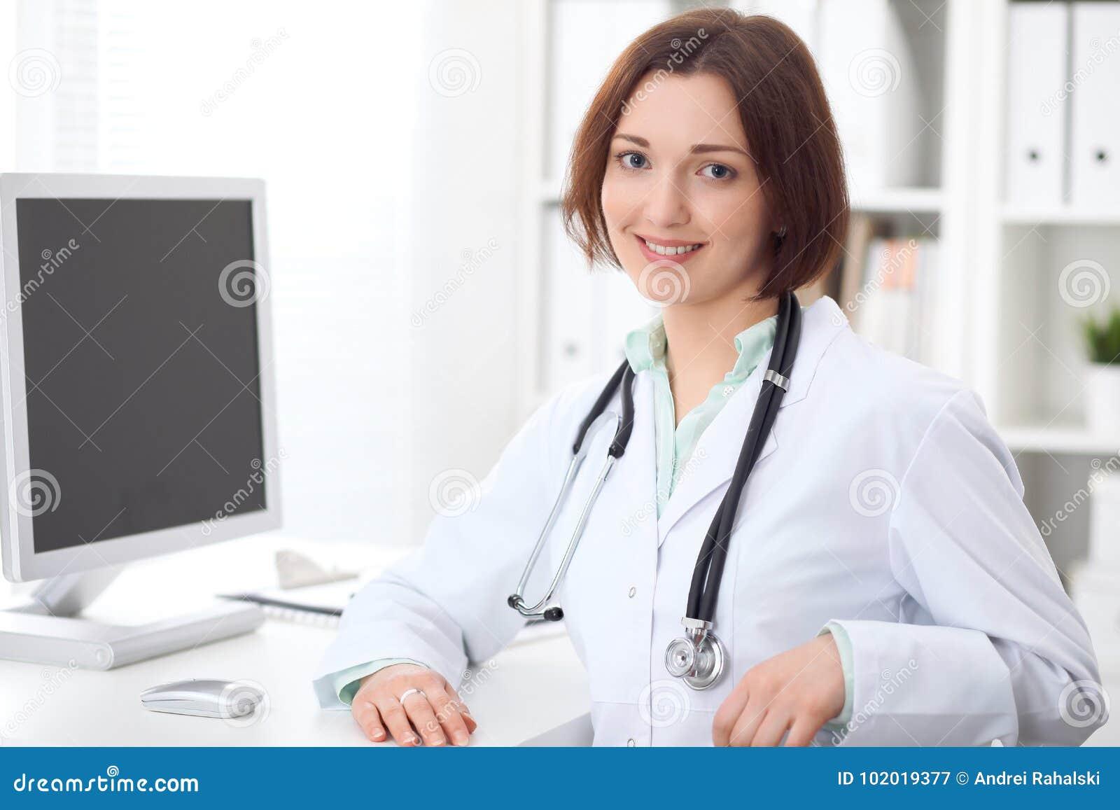 Giovane medico femminile castana che si siede ad uno scrittorio e che lavora al computer all ufficio dell ospedale