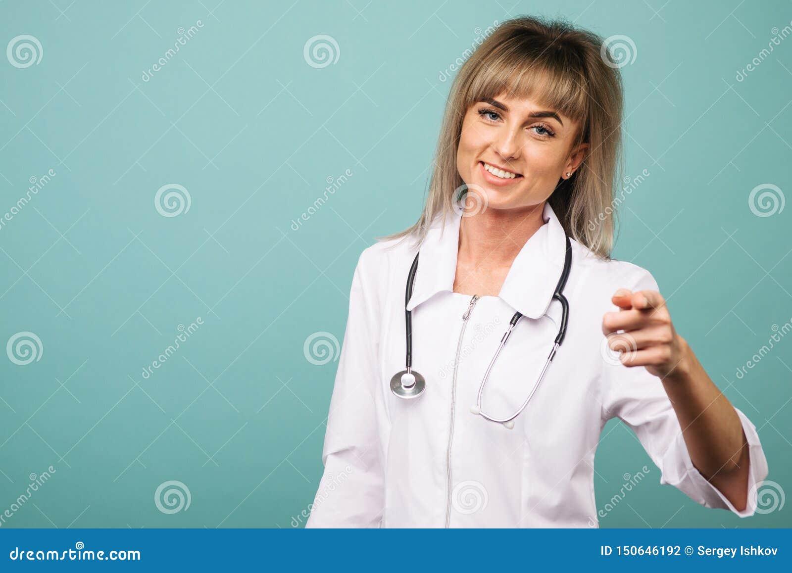 Giovane medico femminile sorridente con i punti di uno stetoscopio nella macchina fotografica con le sue dita