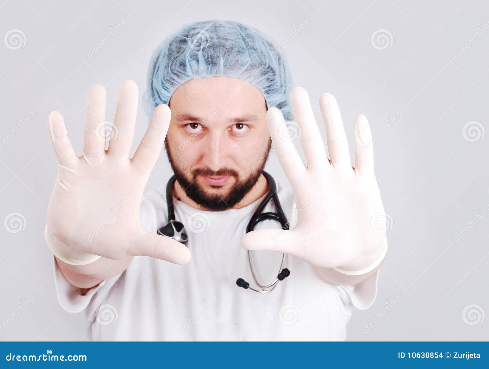 Giovane medico maschio con le mani nella parte anteriore e nella chirurgia