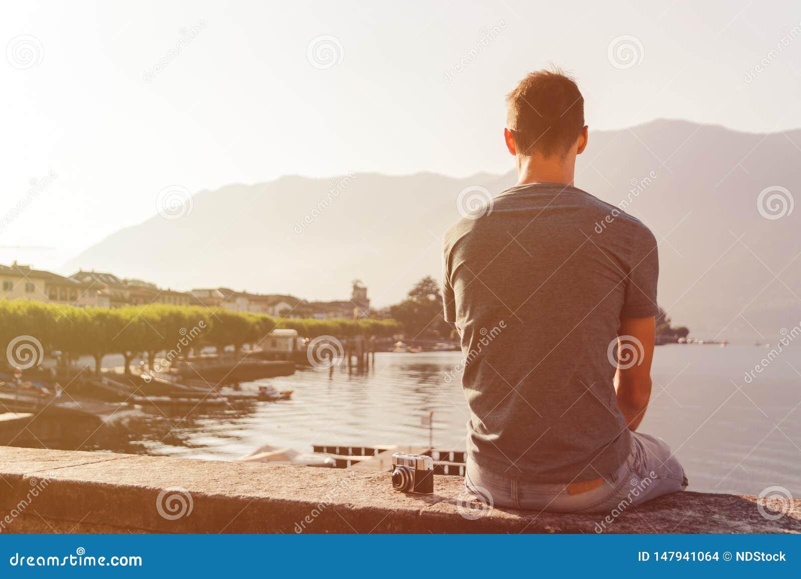 Giovane messo su una parete con una macchina fotografica d annata davanti alla passeggiata del lago in Ascona