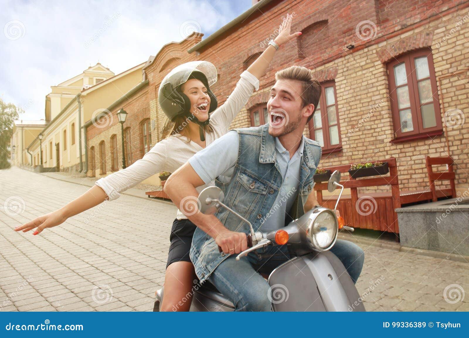 Giovane motorino felice di guida delle coppie in città Viaggio bello della giovane donna e del tipo Concetto di vacanze e di avve