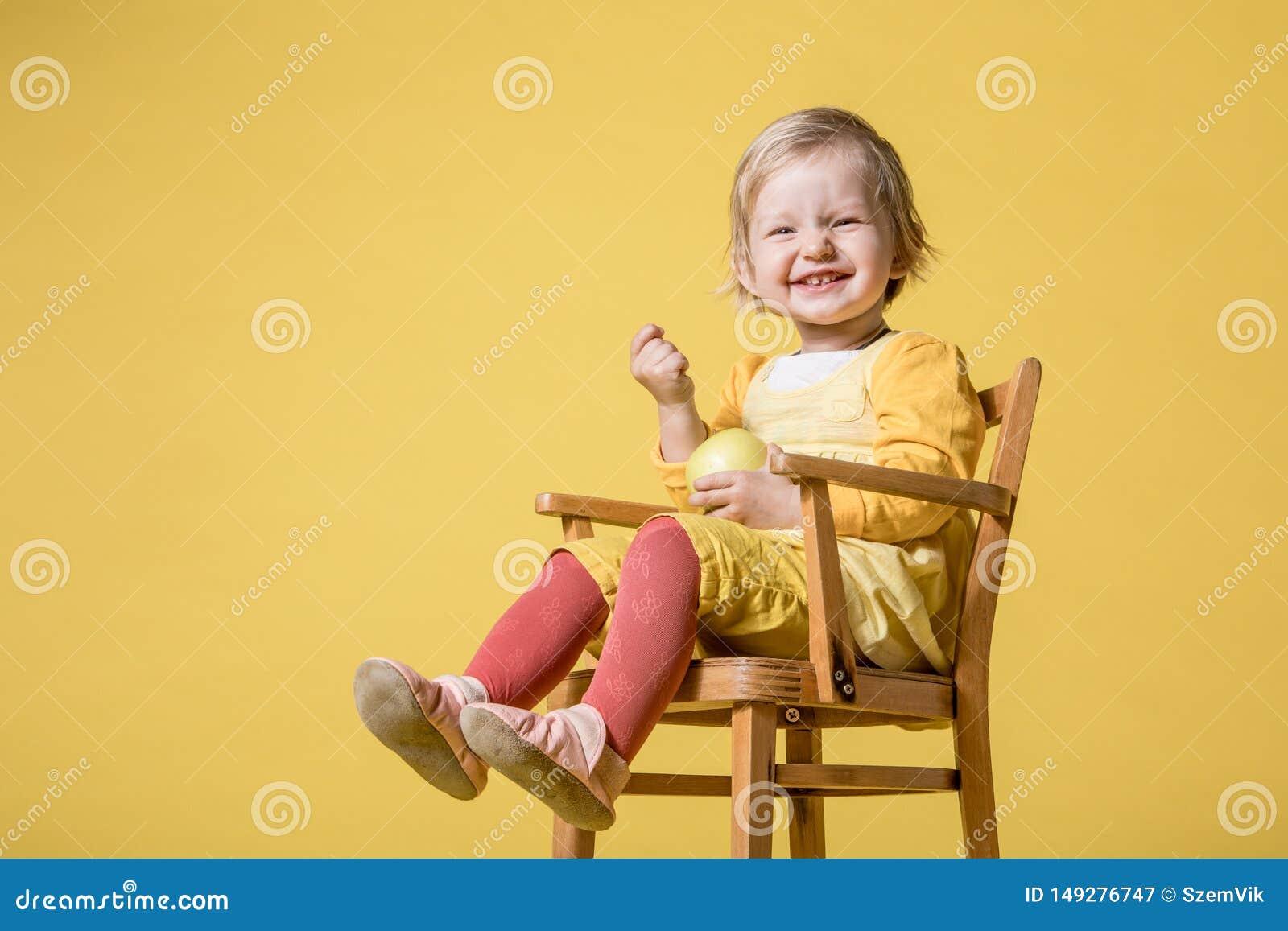 Giovane neonata in vestito giallo su fondo giallo