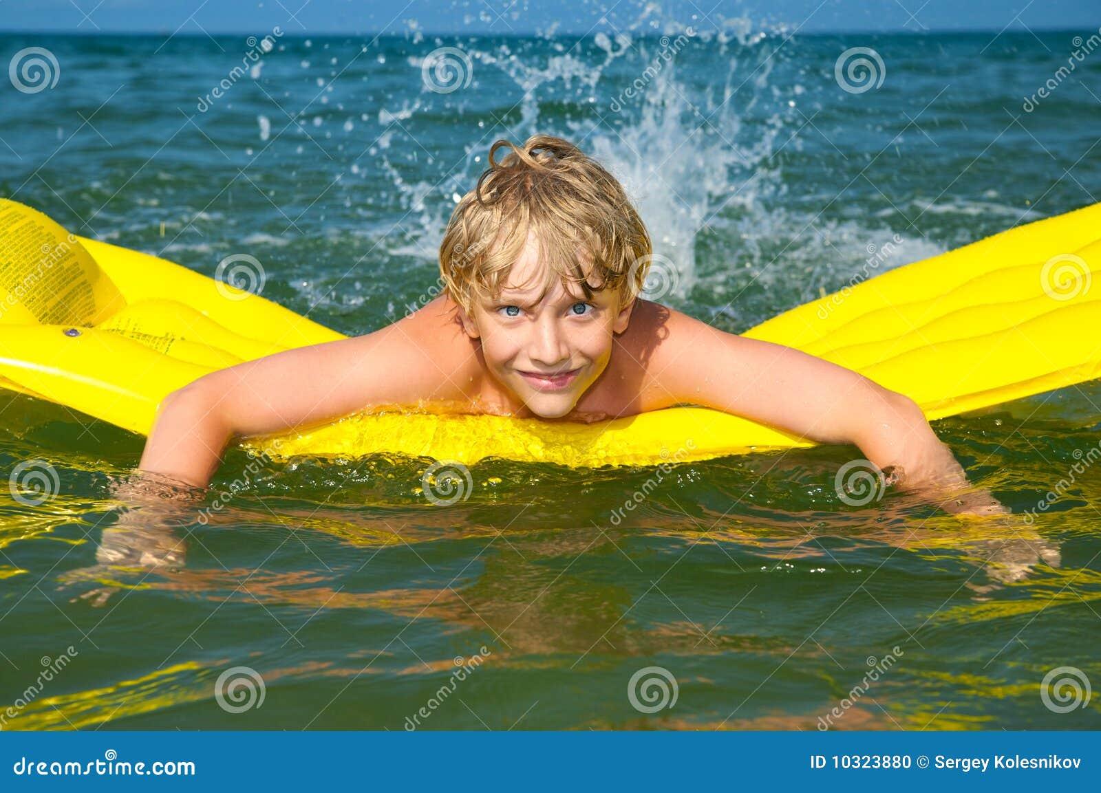 Giovane nuoto del ragazzo sul materasso nel mare