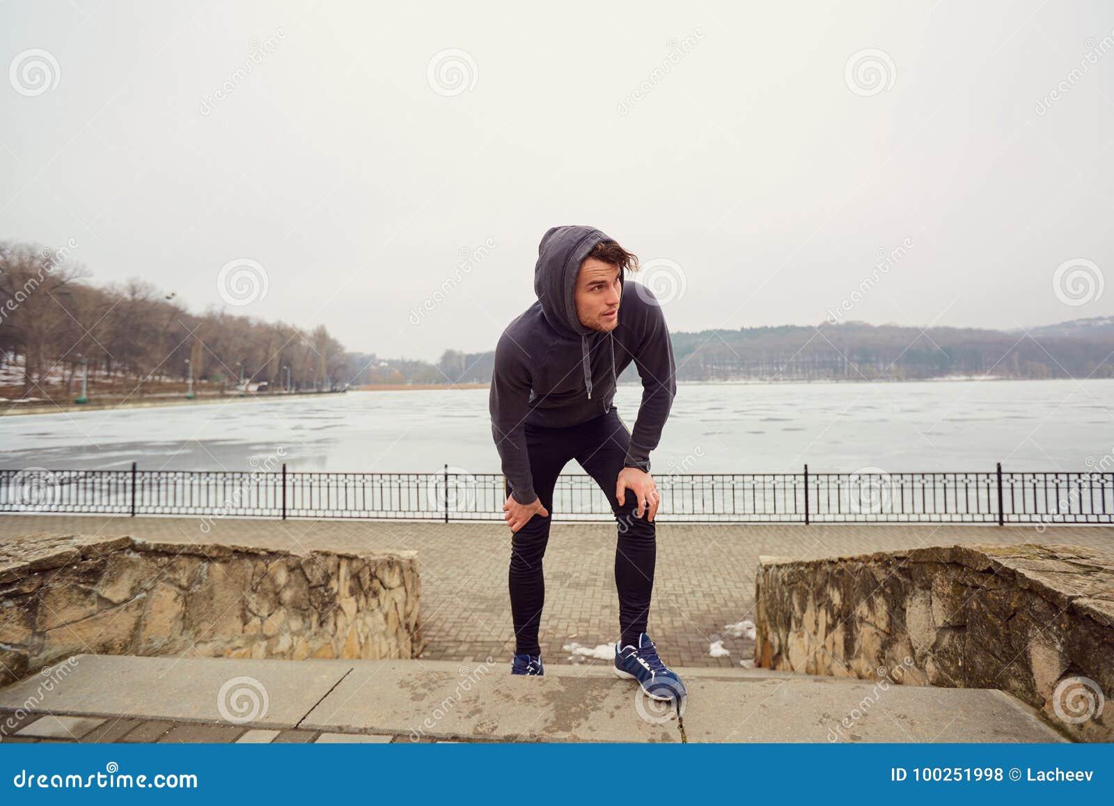Giovane omosessuale in abiti sportivi in un parco per un trotto