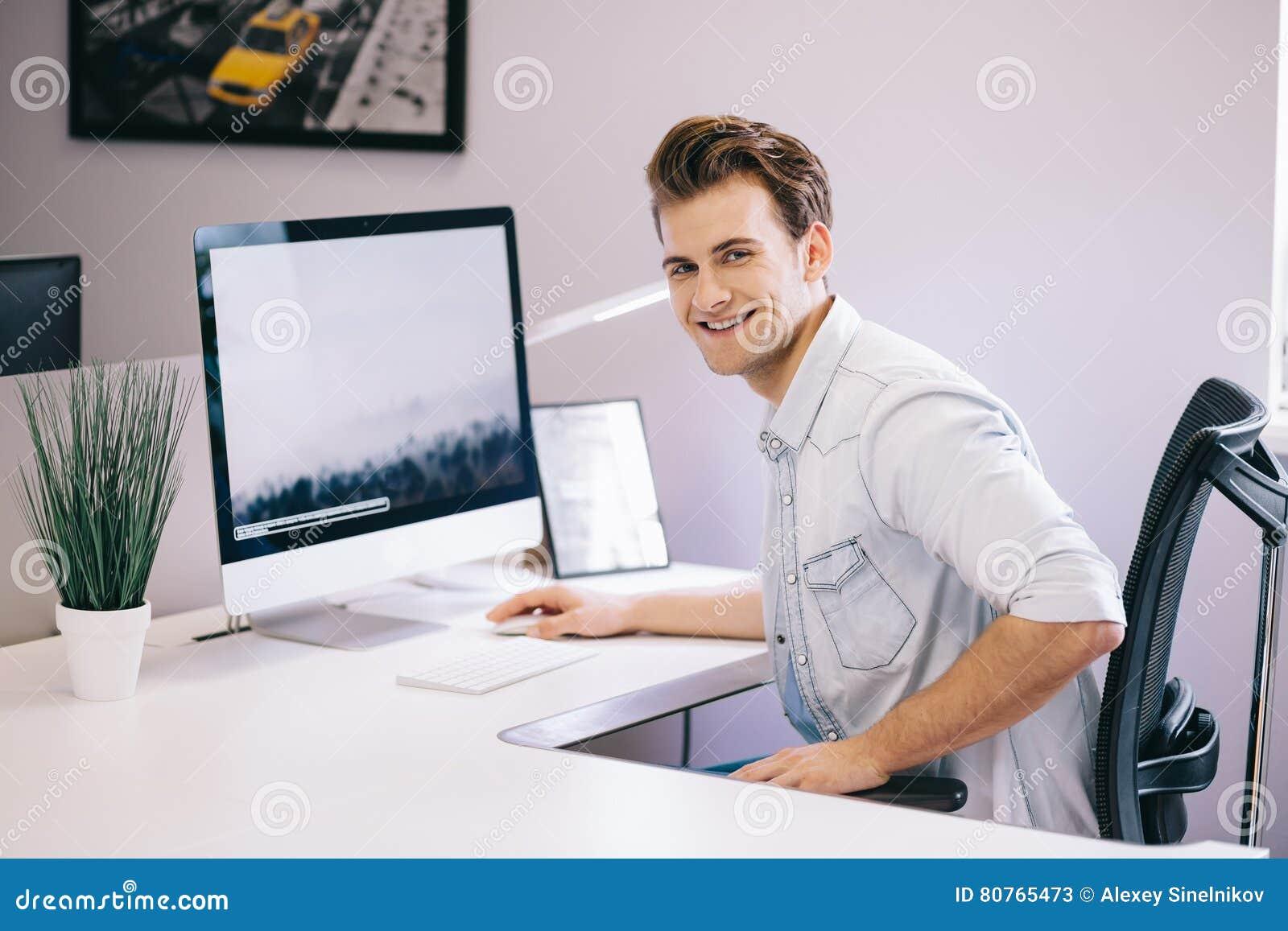 Giovane operaio che si siede in un ufficio al computer Free lance in una camicia bianca Il progettista si siede davanti alla fine