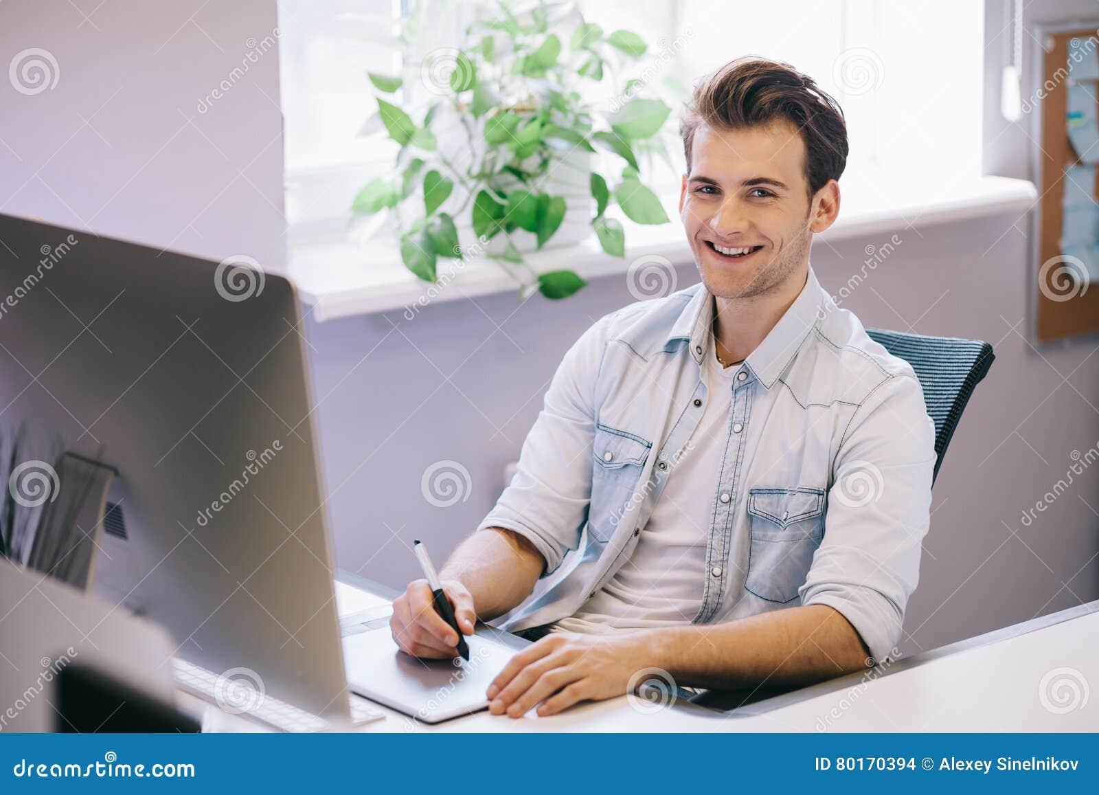 Giovane operaio che si siede in un ufficio al computer Free lance in una camicia blu Il progettista si siede davanti alla finestr
