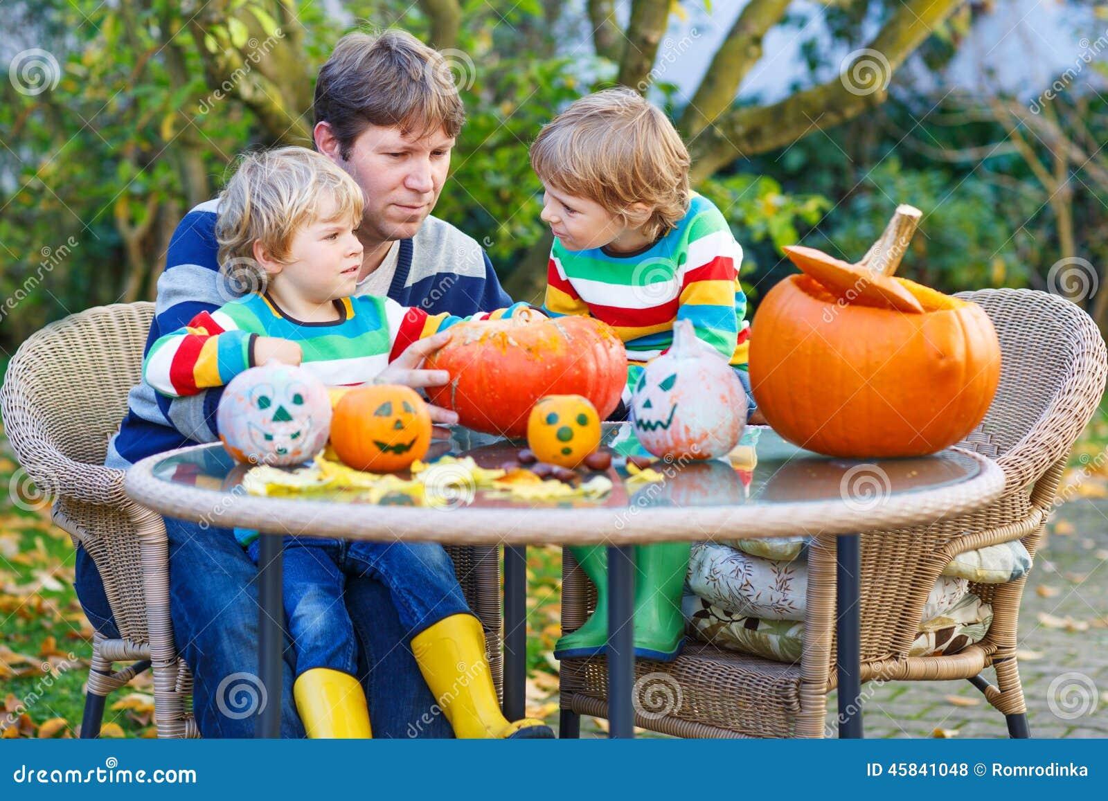 Giovane padre e due piccoli figli che fanno presa-o-lanterna per ciao