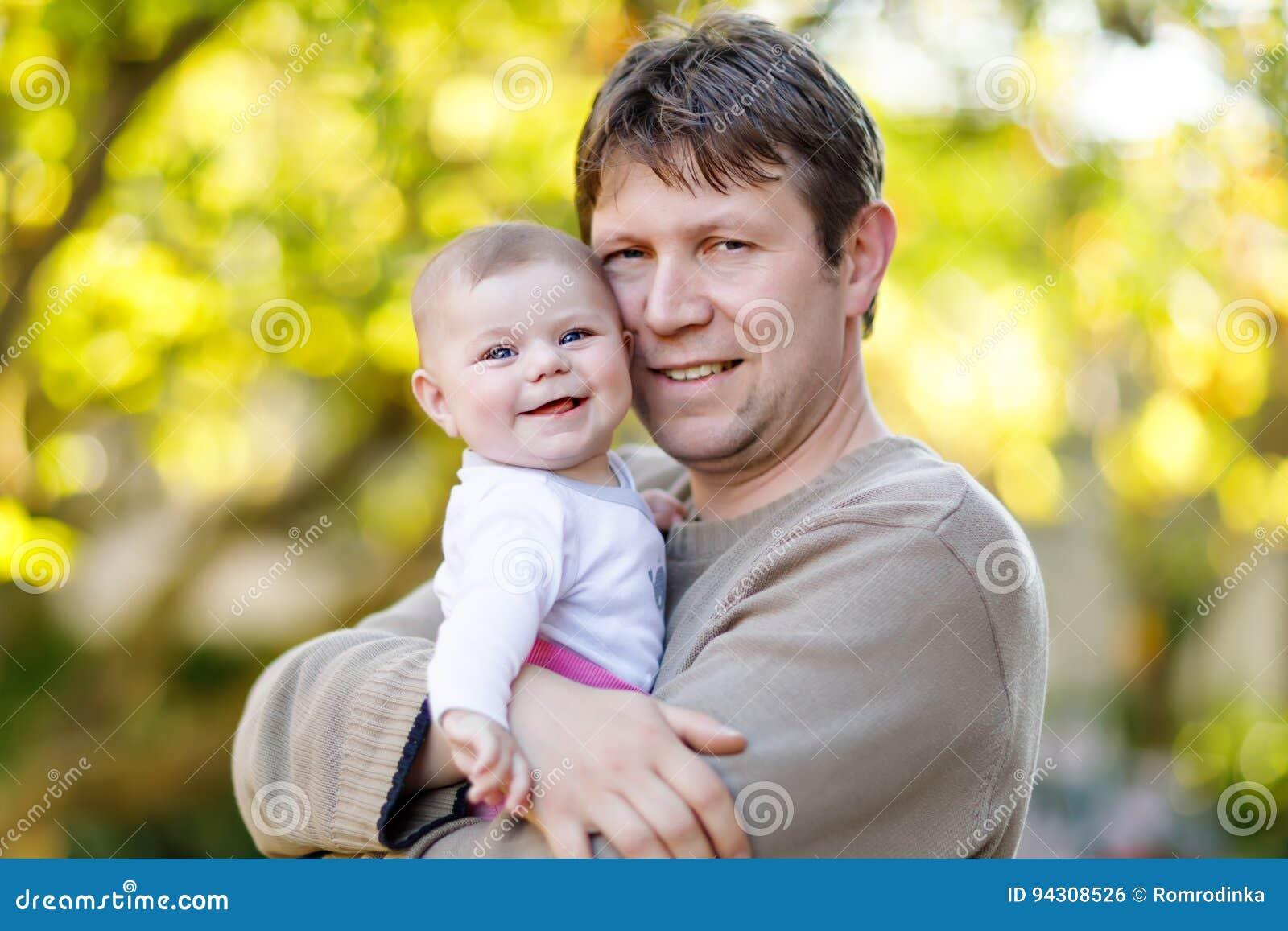 Giovane padre fiero felice con la figlia del neonato, ritratto della famiglia insieme