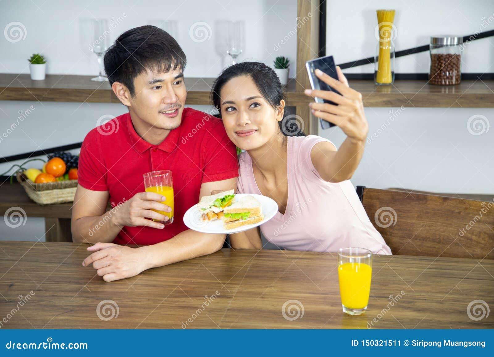 Giovane panino adorabile romantico di manifestazione del selfie delle coppie nella cucina