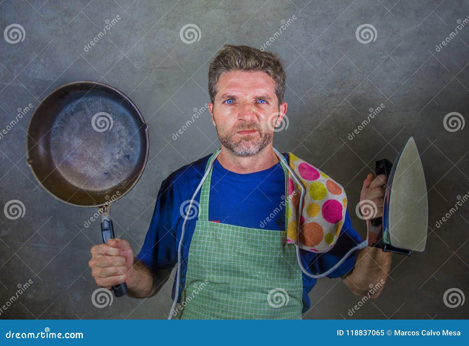 Giovane pentola attraente e ferro pigri sollecitati ed enormi della cucina della tenuta dell uomo nello sforzo e nell espressione