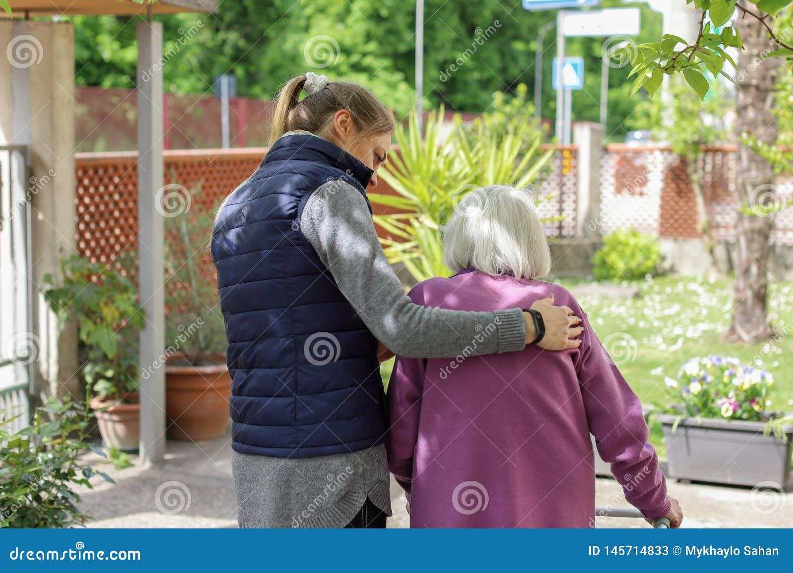 Giovane personale sanitario che cammina con la donna anziana nel giardino