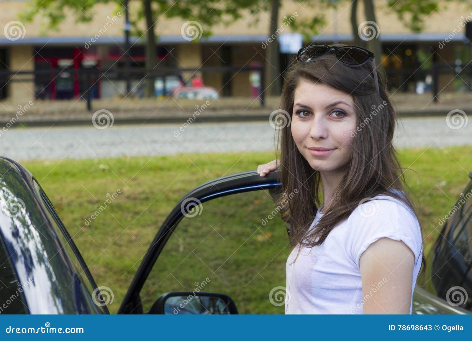 Giovane posa castana vicino all automobile
