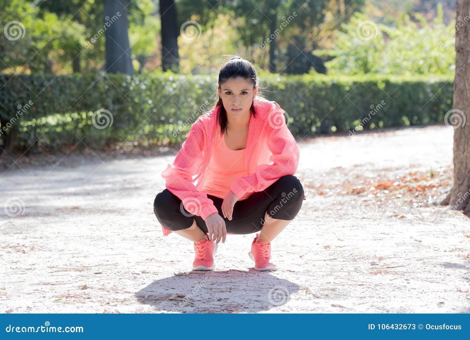 Giovane posa felice ed attraente della donna del corridore di sport rilassata al parco della città che guarda misura e sana dopo