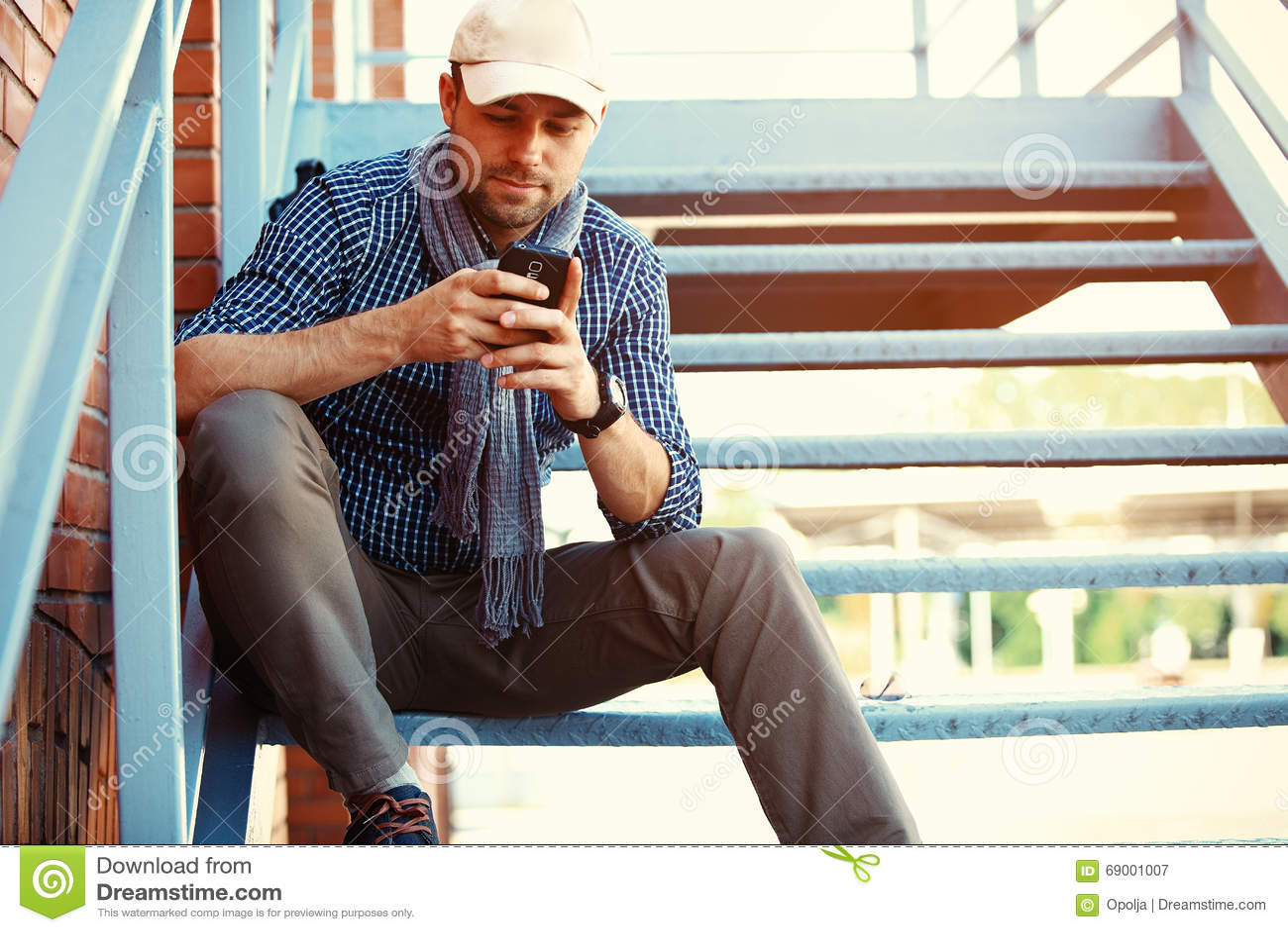 Giovane professionista dell uomo d affari sullo smartphone che cammina in via facendo uso del messaggio mandante un sms degli sms