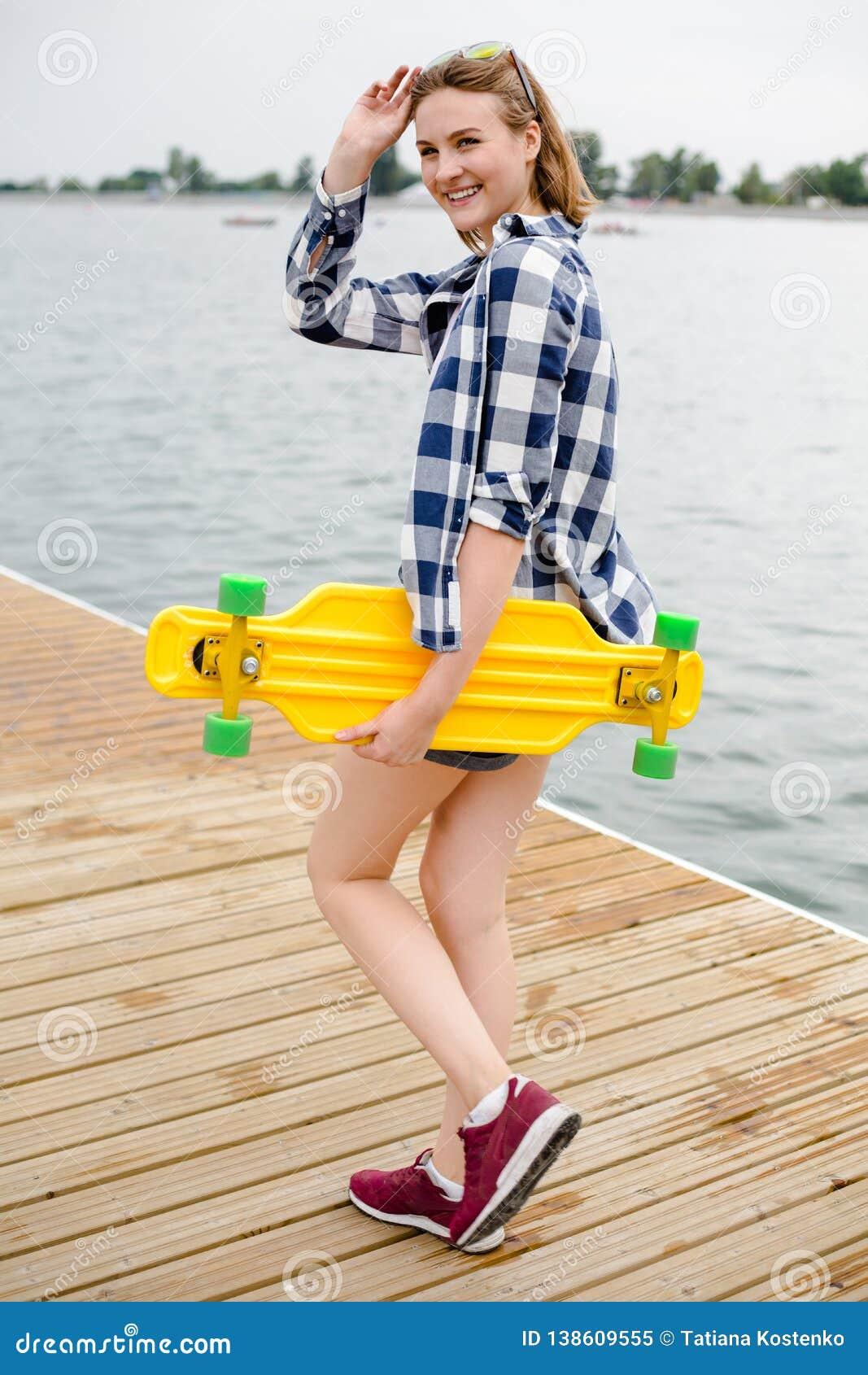 Giovane ragazza allegra in attrezzatura dei pantaloni a vita bassa che tiene longboard giallo in sua mano e che cammina su un pil