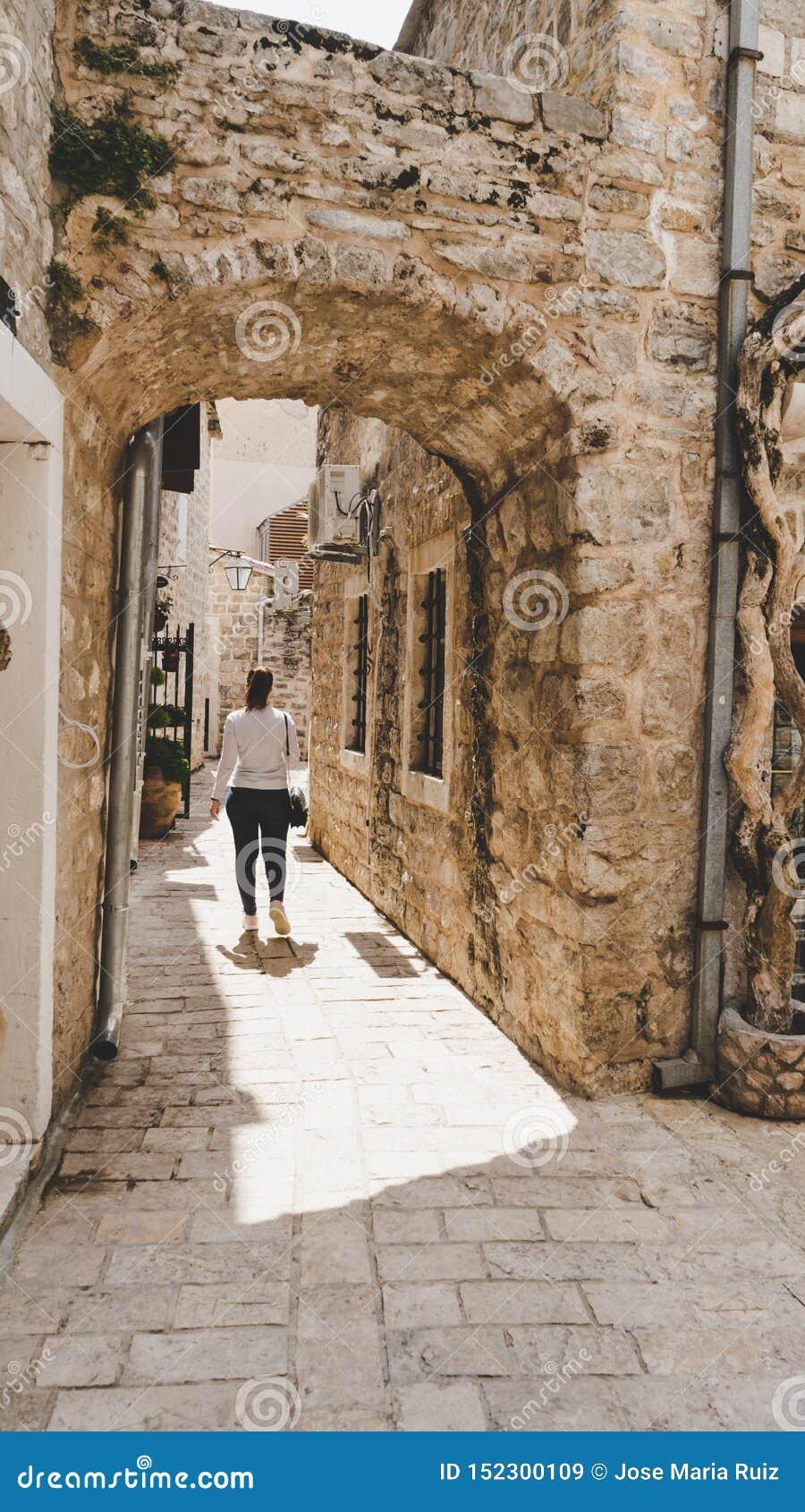 Giovane ragazza bianca che prende le immagini nelle piccole vie strette di vecchia città di Budua, Montenegro Donna che cammina f