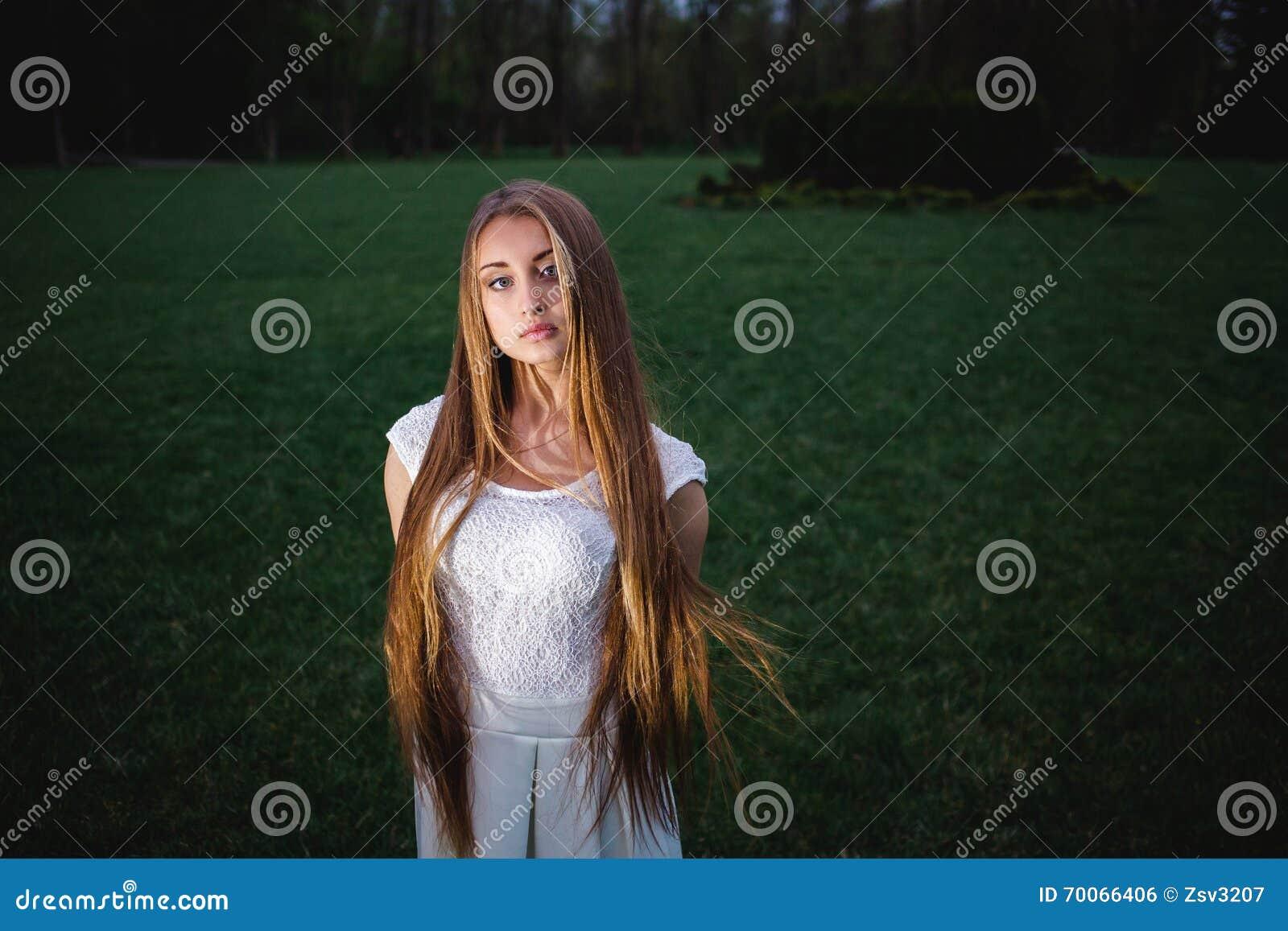 Giovane ragazza bionda illuminata da una lanterna magica nel giardino di mistero di notte