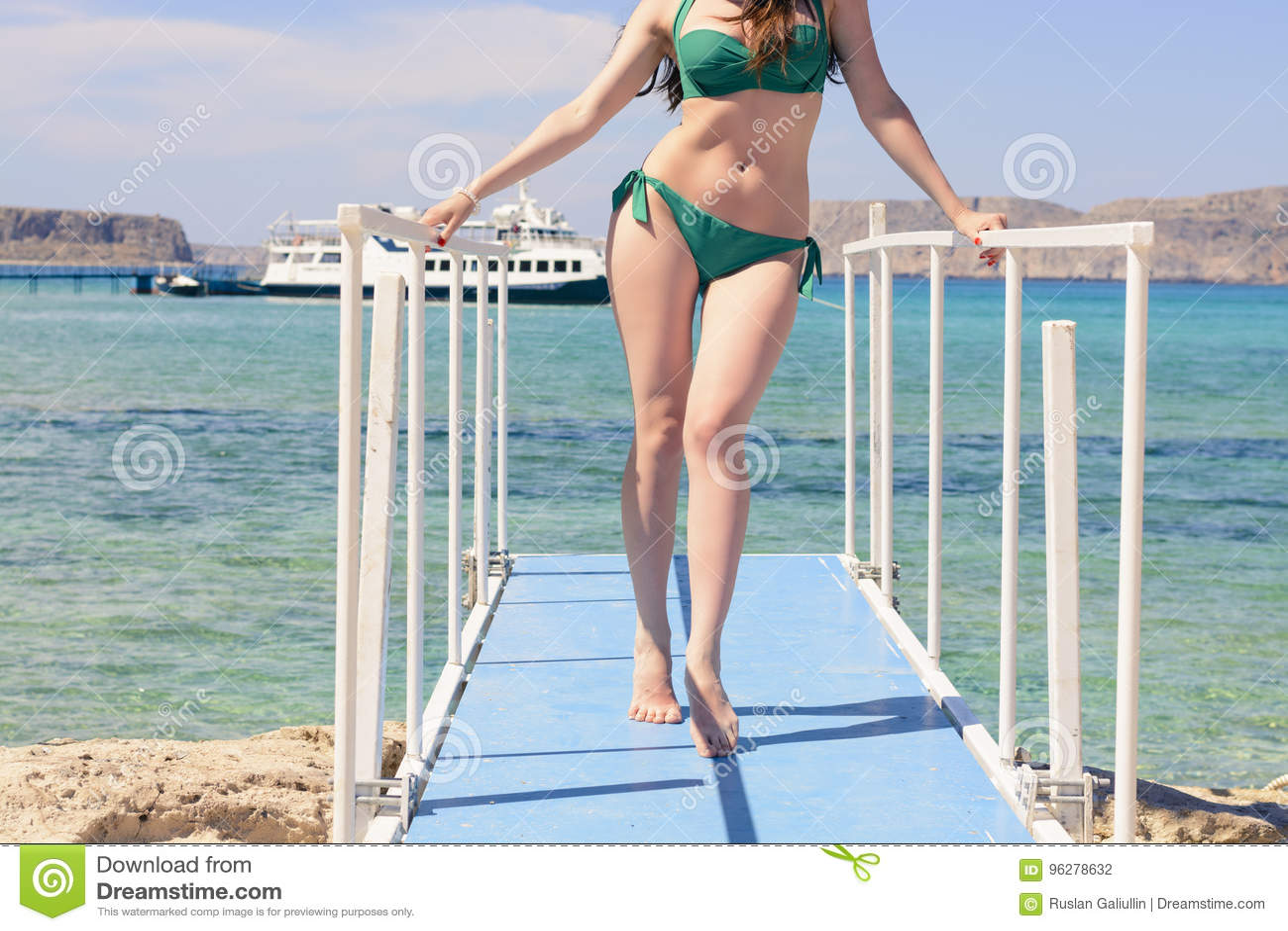 Giovane ragazza caucasica in un costume da bagno verde sul pilastro blu, dal mare ionico blu del fondo, Balos, Grecia