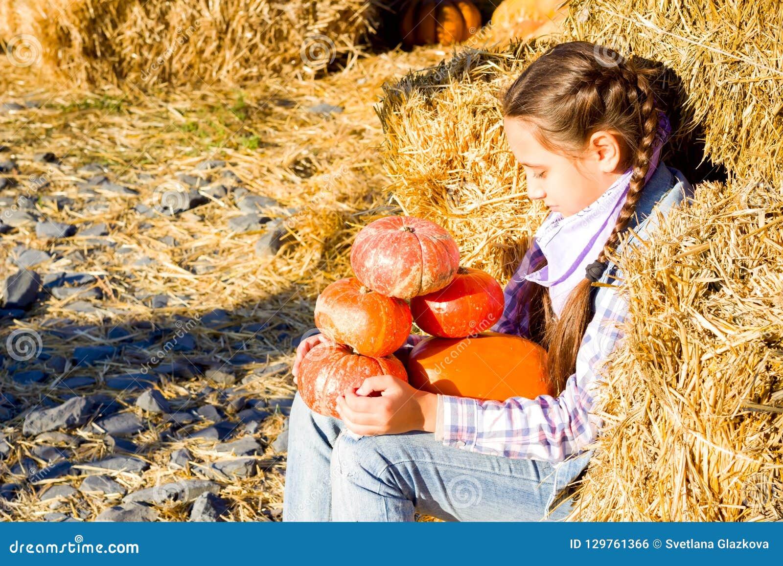 Giovane ragazza dell adolescente che si siede sulla paglia con i pumkins sul mercato dell azienda agricola Famiglia che celebra r
