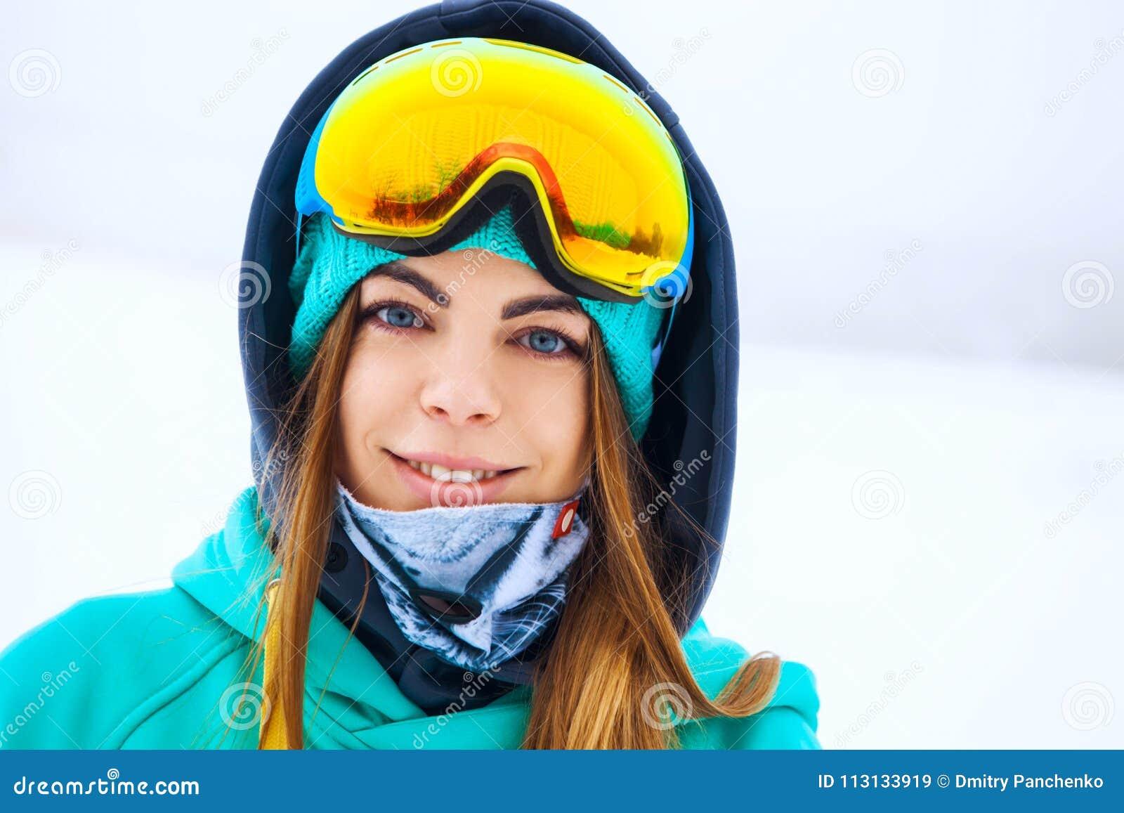 Giovane ragazza felice dello snowboarder negli occhiali di protezione dello snowboard