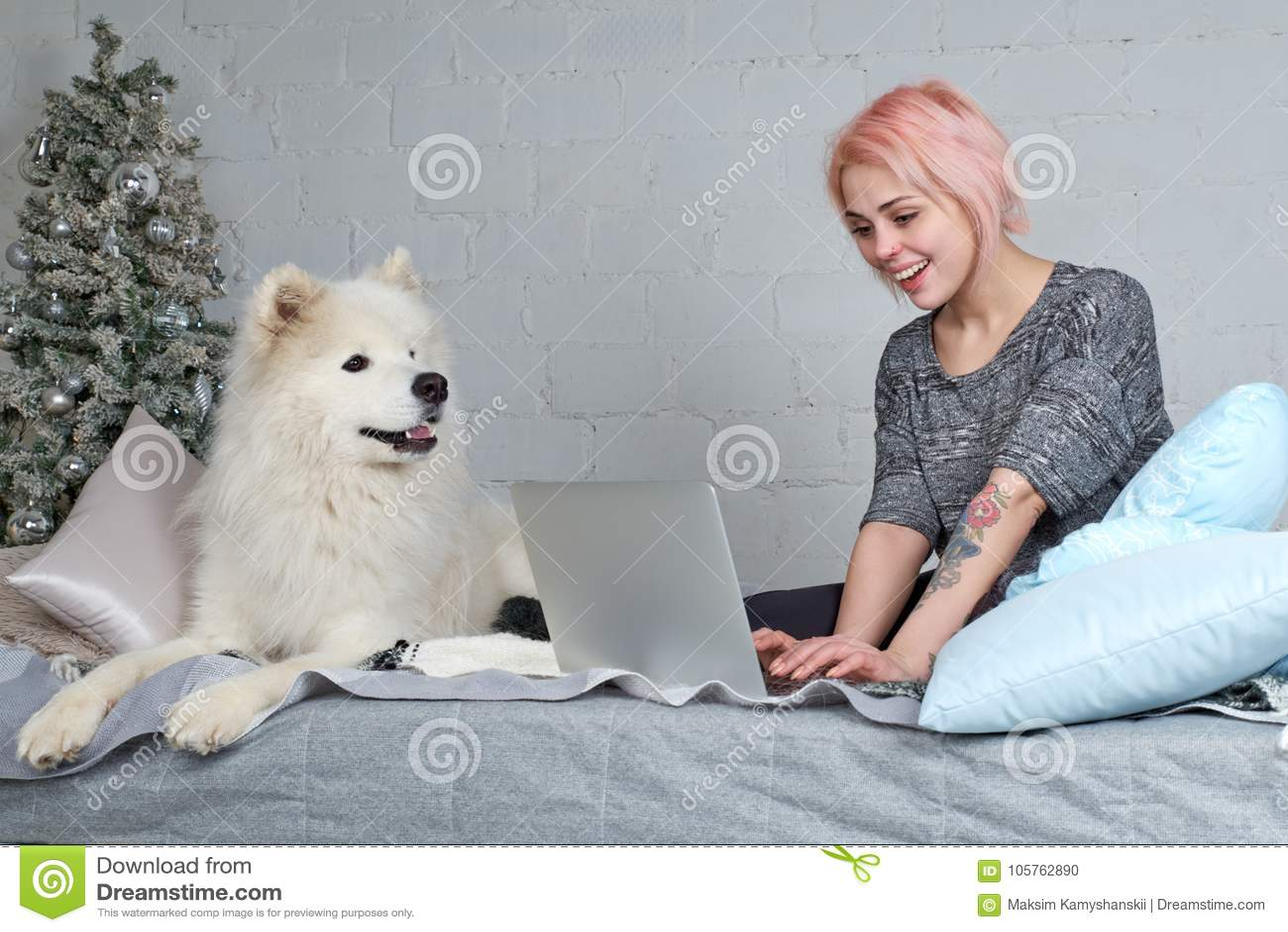 Giovane ragazza graziosa con capelli biondi che funzionano con il computer portatile sul SOF