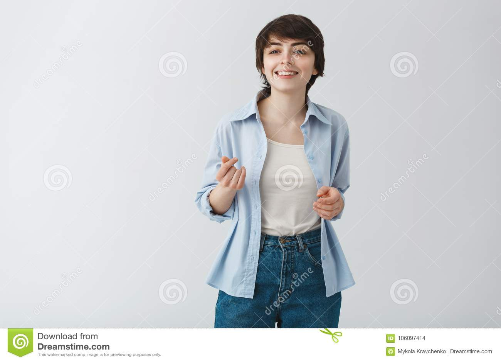 Giovane ragazza graziosa dello studente con i capelli di scarsità ed i grandi occhi che sorride con i denti, dancing e divertente