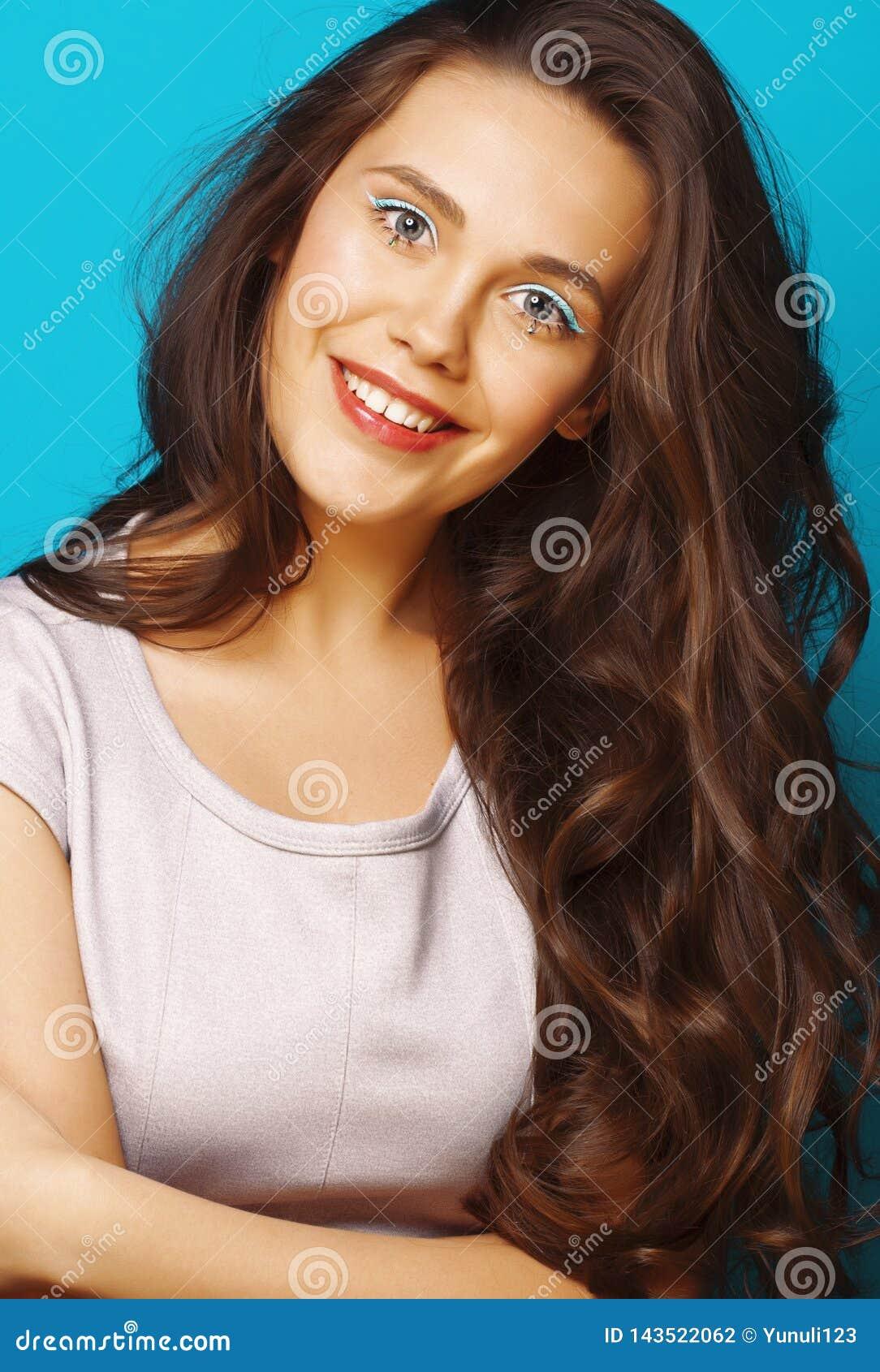 Giovane ragazza moderna adolescente graziosa che posa felice emozionale su fondo blu, concetto della gente di stile di vita