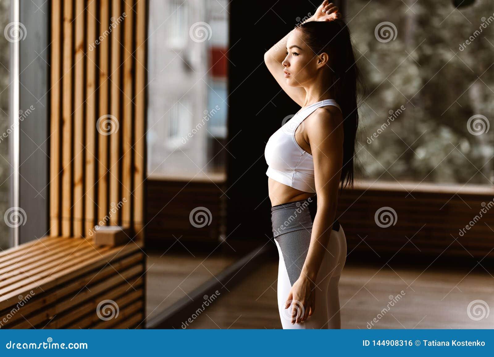 Giovane ragazza mora esile vestita nella cima di sport e nei supporti bianchi delle calzamaglia nella palestra