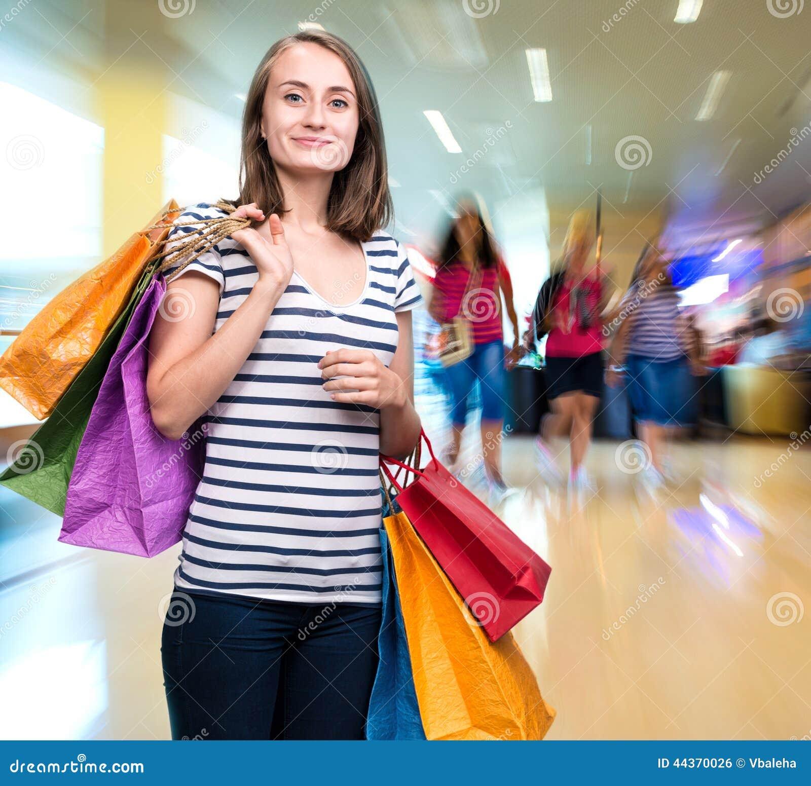 Giovane ragazza sorridente con i sacchetti della spesa