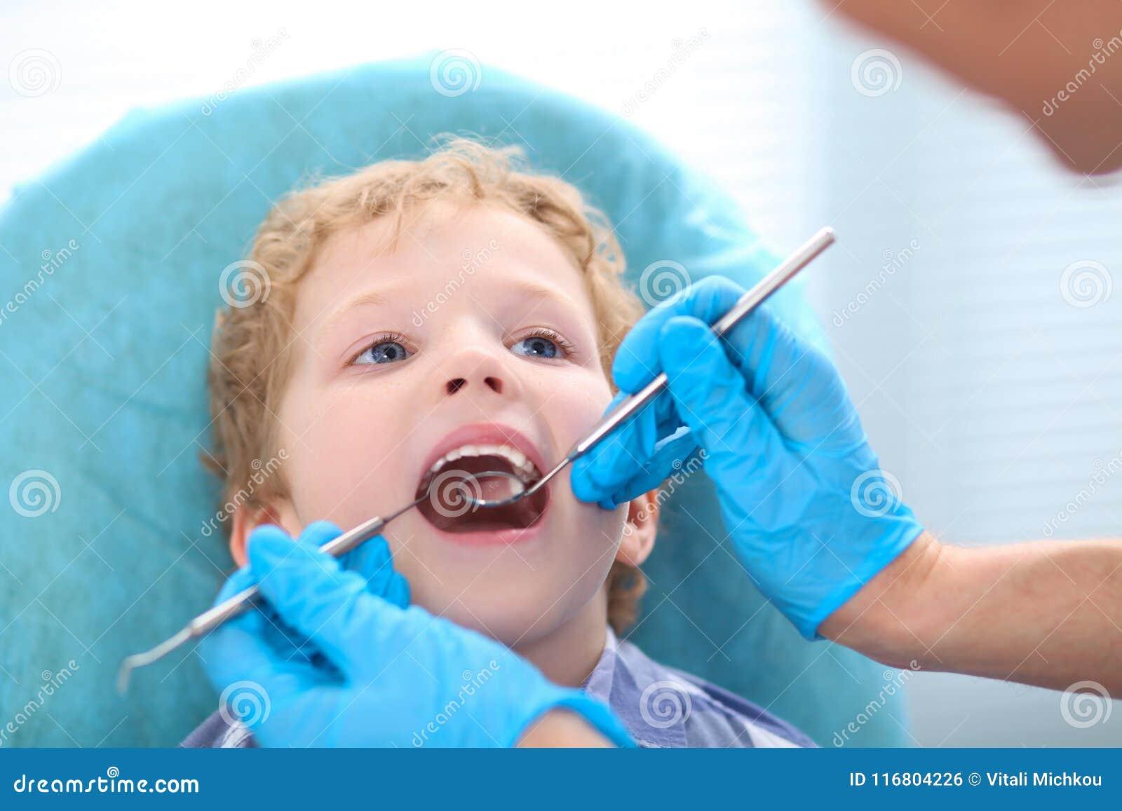 Giovane ragazzo caucasico riccio alla clinica del ` s del dentista