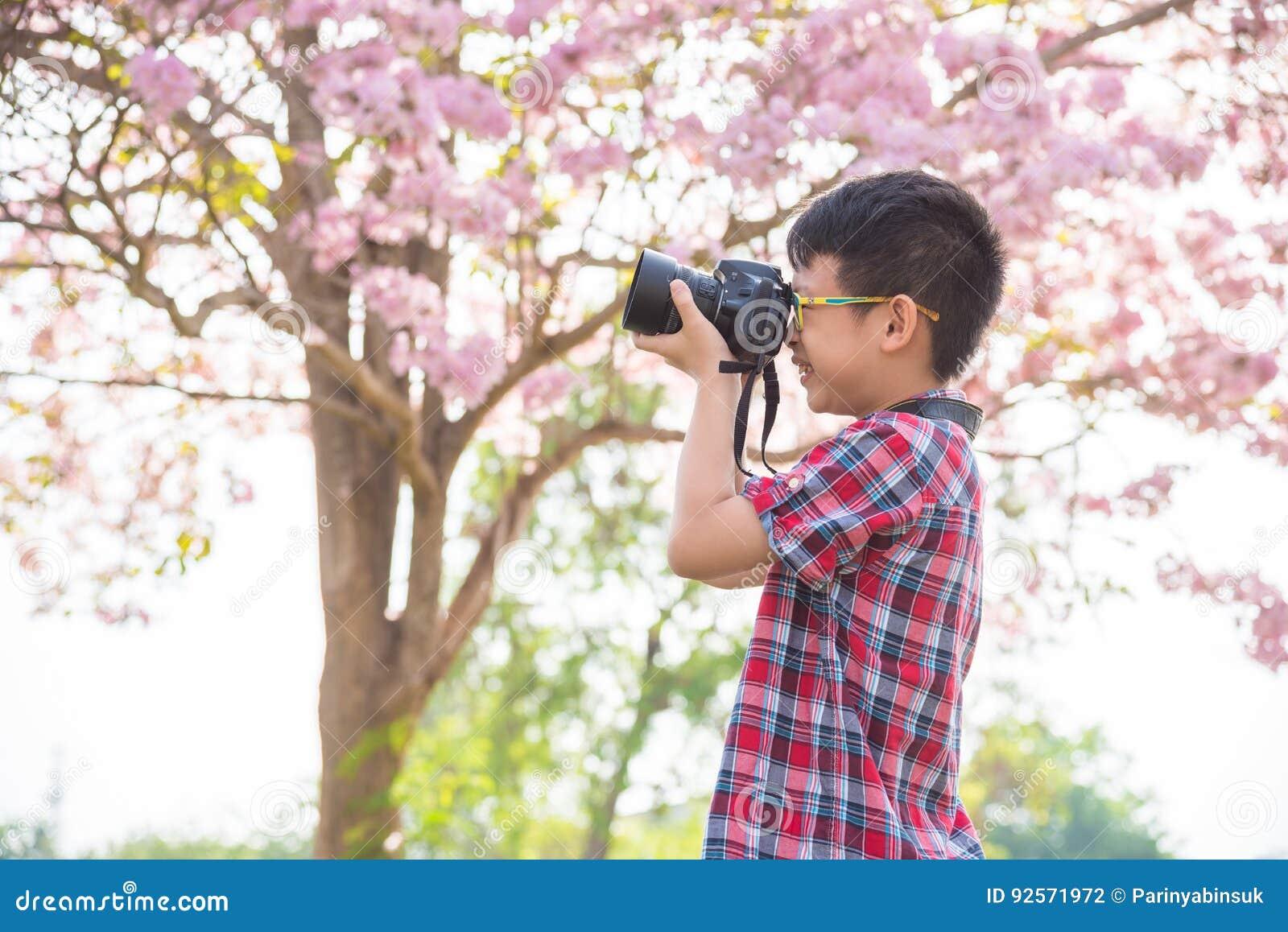 Giovane ragazzo che prende foto dalla macchina fotografica in parco
