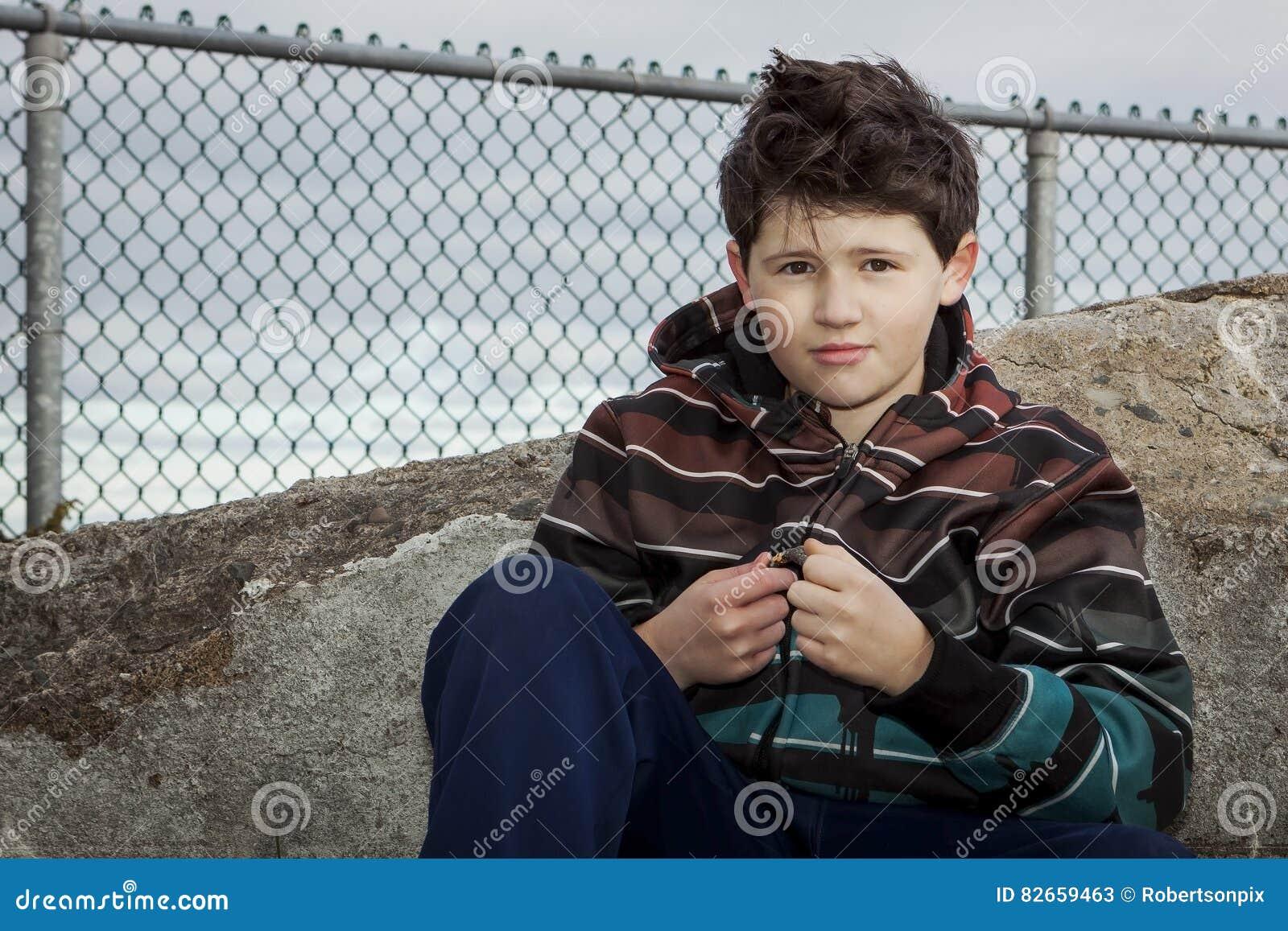 Giovane ragazzo che si siede su una roccia davanti ad un recinto Under del collegamento a catena Grey Sky nuvoloso