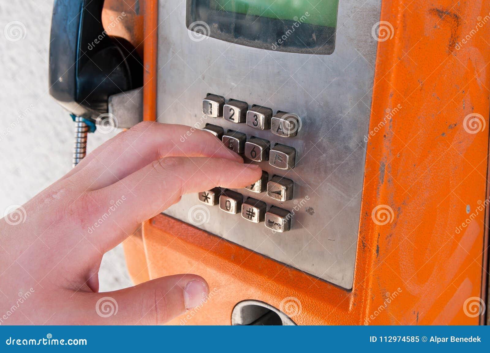 Giovane ragazzo che tocca un vecchio telefono pubblico arancio inutilizzato e unfunctional