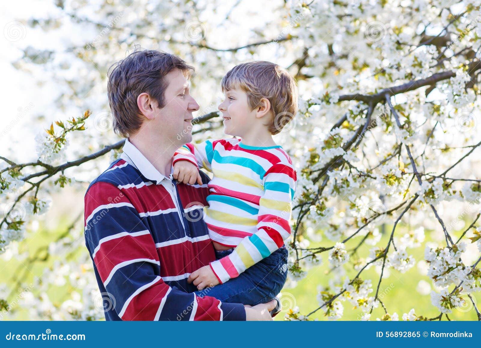 Giovane ragazzo del bambino e del padre in giardino di fioritura