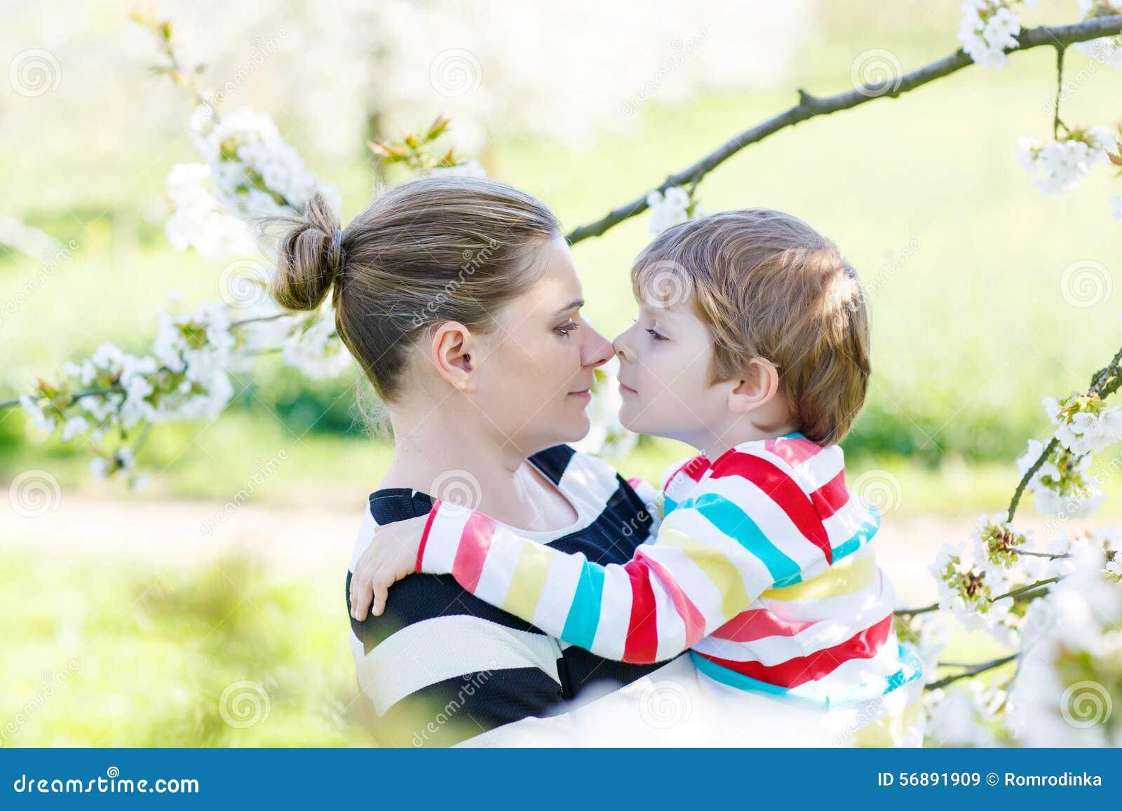 Giovane ragazzo del bambino e della madre divertendosi nel giardino di fioritura