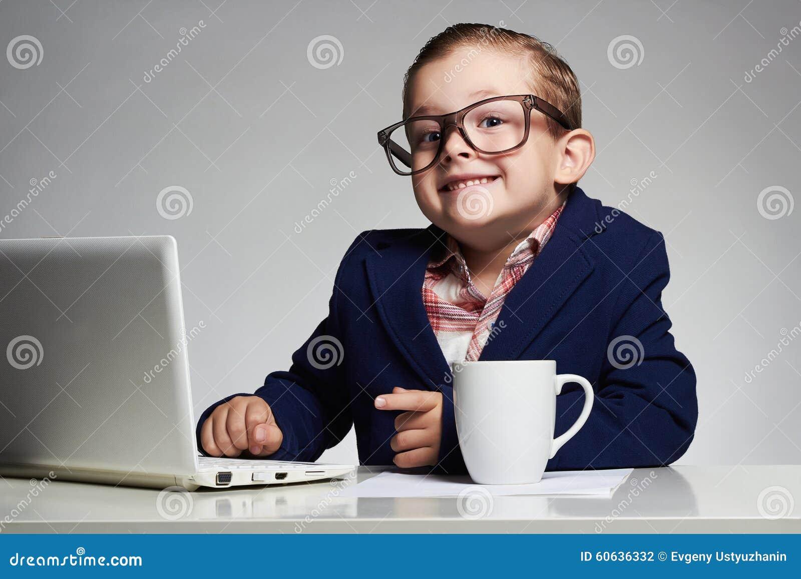 Giovane ragazzo di affari bambino sorridente in vetri piccolo capo in ufficio
