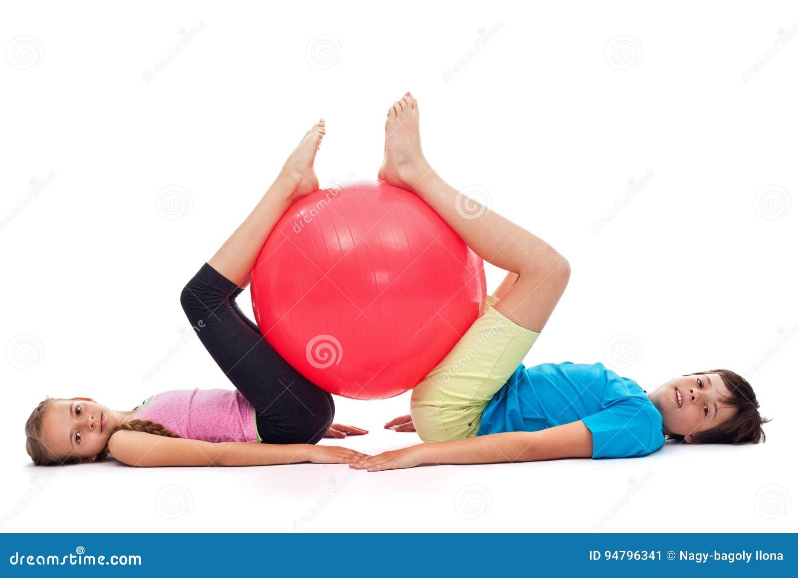 Giovane ragazzo e ragazza che si esercitano con una grande palla di gomma relativa alla ginnastica