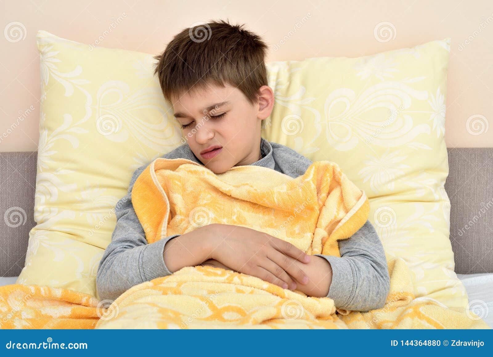 Giovane ragazzo malato che si siede a letto         6198